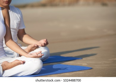 Cropped image of young people meditating on the beach in the morning