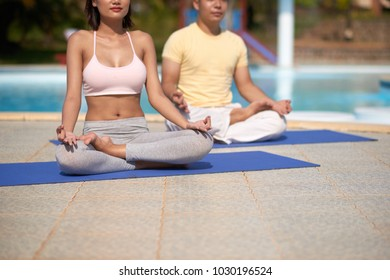 Cropped image of young people meditating in lotus position in the morning