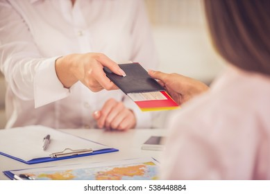Cropped image of young pretty travel agent giving tickets to client