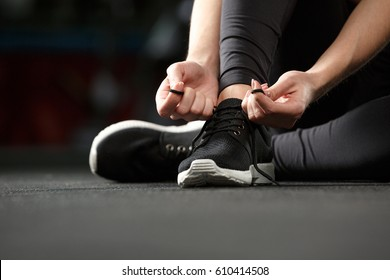 Cropped image of young strong fitness lady sitting and tie laces in gym.