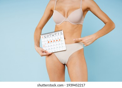 Cropped image young woman in beige underwear point index finger on female periods calendar for checking menstruation days isolated on blue background studio. Medical healthcare gynecological concept