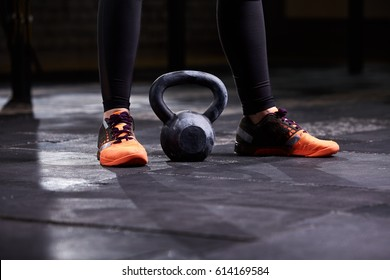 Cropped image of young woman, legs in the black leggings, orange sneakers and kettlebell. workout at gym