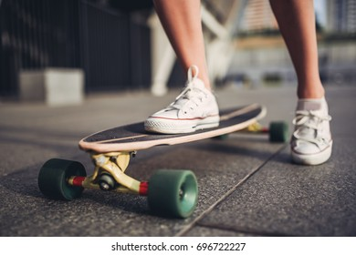 Cropped image of young woman is skateboarding in the city. Female teenager with long board outdoors.