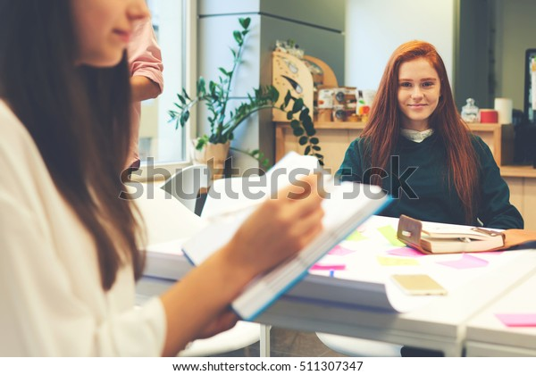 Cropped image of young woman takes notes in a notebook while her female colleague creative designer looking at the camera. Student girl sitting in campus interior during break of college lectures