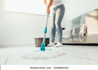 Cropped image of young woman in using a mop while cleaning floor in the house