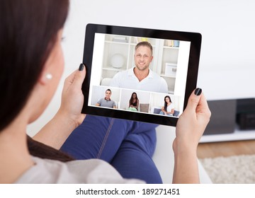 Cropped image of young woman using tablet for video conference at home