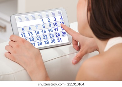 Cropped image of young woman using calendar on digital tablet at home