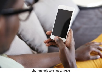 Cropped indoor image of unrecognizable dark-skinned man relaxing on couch in living room, using home wi-fi on modern mobile phone with blank copy space screen for your text or advertising content
