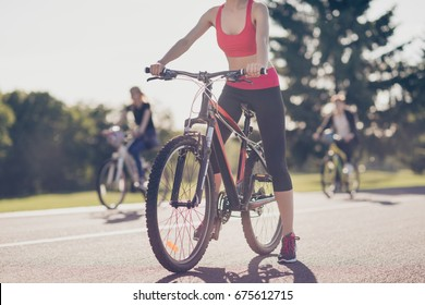 Cropped low angle photo of athletes cycling on the road outdoors, focused on a girl, she stopped, in trandy outfit, sneakers