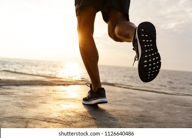 Cropped male legs of healthy sportsman wearing shorts and sneakers running along pier at seaside during beautiful sunrise