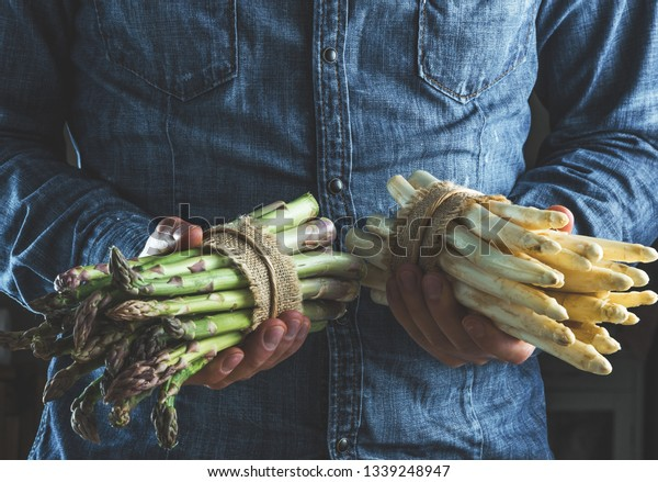 cropped of man holding bunches of green and white tied asparagus