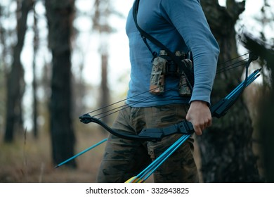 Cropped man with hunter bow goes through the wood