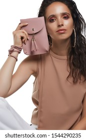 Cropped medium shot of a young dark-haired lady in a beige blouse hiding her face behind a powder pink rectangular leather clutch with a long handle, a snap button fastening and leather tassels.