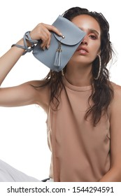Cropped medium shot of a young dark-haired lady in a beige blouse hiding her face behind a gray-blue rectangular leather clutch with a long handle, a snap button fastening and leather tassels.