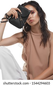 Cropped medium shot of a young dark-haired lady in a beige blouse hiding her face behind a black rectangular leather clutch with a long handle, a snap button fastening and leather tassels.