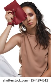 Cropped medium shot of a young dark-haired lady in a beige blouse showing a red rectangular leather clutch with a long handle, a snap button fastening and leather tassels.