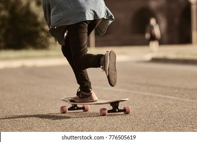 Cropped outdoor picture of male teenager skateboarding in city with one foot placed on board and pushing off with the other. Stylish skateboarder riding longboard. Selective focus on boy's foot