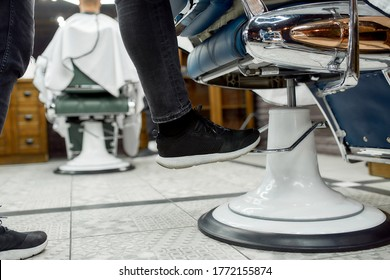 Cropped photo of adjustable barber chair. Barber adjusting barber chair while working in the modern barbershop. Selective focus, close up. Hair salon. Barbershop concept