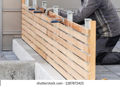 Cropped photo of adult handyman or workman repairing new wooden fence near house using c-clamp