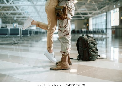 Cropped photo of American military man embracing his wife in waiting room. His spouse is glad to see him after long time apart. Focus on their legs. Homecoming and military concept