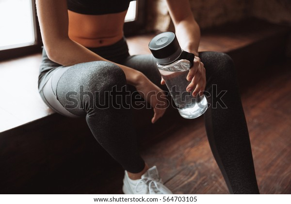 Cropped photo of attractive fitness woman sitting in gym and holding bottle of water.