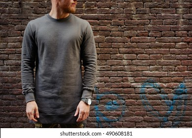 A cropped photo of a bearded hipster guy wearing blank gray long sleeve t-shirt while standing on a brick wall background on a street. Empty place for you logo or design.