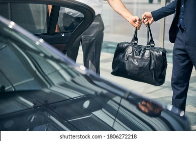 Cropped photo of a black bag being passed from driver to passenger standing by the car