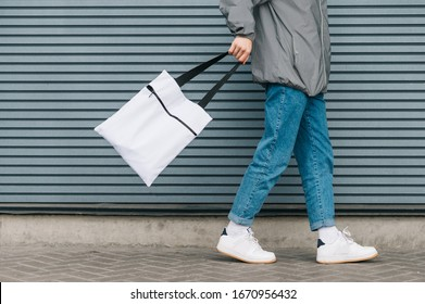 Cropped photo of the bottom of a young man in stylish clothes walking on the background of a gray wall with an white eco bag in his hand. Eco friendly. Reusable bag in young man's hand. Copy space