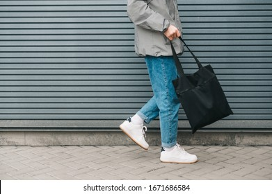 Cropped photo of the bottom of a young man in stylish clothes walking on the background of a gray wall with an black eco bag in his hand. Eco friendly. Reusable bag in young man's hand. Copy space