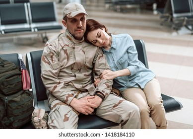 Cropped photo of calm tired woman situating near her husband in military uniform indoors. She is putting her head on the man's shoulder while hugging him. Homecoming concept
