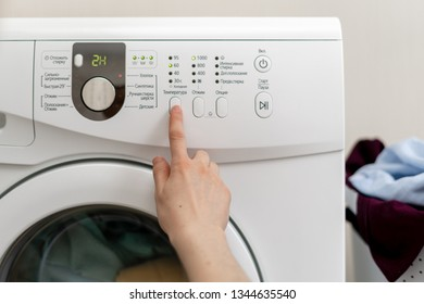 Cropped photo of choosing of laundry program. Woman select temperature on panel of washing machine inside bright apartment light interior