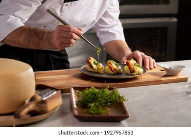 Cropped photo Close-up hands of male cook adding greens finishing dish, decorating meal in the end. gastronomy, food, nutrition, cafe concept
