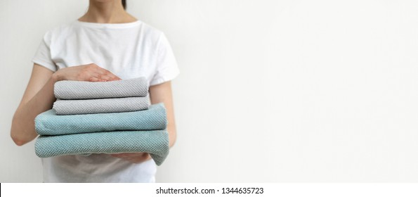 Cropped photo of confident woman holding clean towels after laundry in hands. She standing against wall inside light flat interior