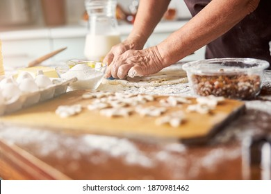 Cropped photo of crafty baker hands cutting dough with special shapers for making cookies