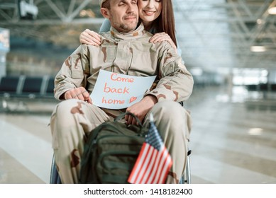 Cropped photo of disabled Caucasian soldier sitting in wheelchair and smiling. He is keeping paper with iscription Come Back Home, little flag of the USA and backpack in arms. Homecoming and military