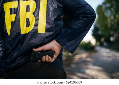 Cropped photo of FBI agent in action with a pistol, rear view