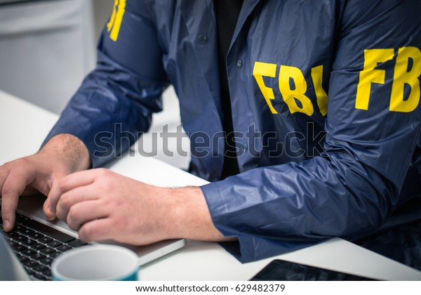 Cropped photo of FBI agent using laptop in office