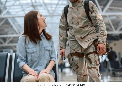 Cropped photo of female model sitting in waiting room. American soldier is standing near his wife and holding dog tag soldier ID in arm. Homecoming concept