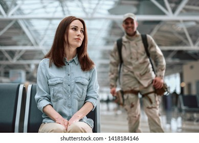 Cropped photo of female model sitting in waiting room. American soldier is standing behind his wife and smiling. Homecoming concept