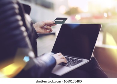 Cropped photo of a girl in black biker leather jacket sitting on a bench outdoors with her laptop, holding credit card in hand and making online purchases. Internet shopping concept. Close up.