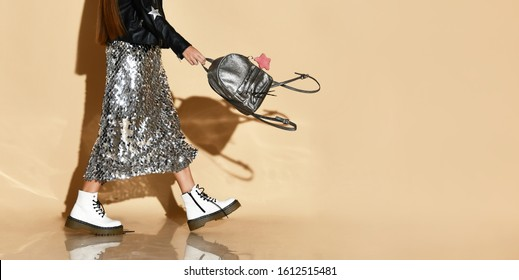 Cropped photo of a girl in a shiny skirt, white shoes. Posing goes sideways with a silver backpack on a beige background. Hipster style, fashion, beauty. Copy space full length