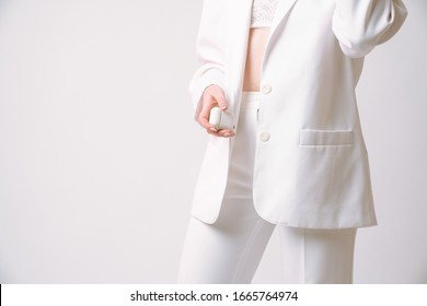 Cropped photo of a gorgeous female in white suit who holds wireless headphones in her hand, isolated over grey background with copyspace