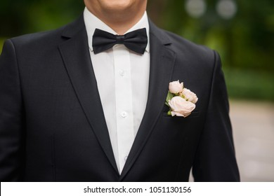 Cropped photo of a groom. Selective focus on a black tuxedo and bow tie, white shirt and rose blossoms in the top pocket.