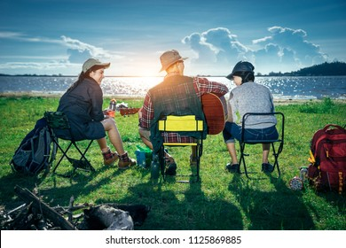 A cropped photo of  group of Asian friends sitting on chairs, singing, playing a guitar and drinking some beer and water together outside the tent while they has camping on Weekend holiday.
