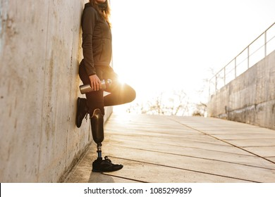 Cropped photo of handicapped woman with prosthesis leg in sportswear standing outdoor over concrete wall with sunlight