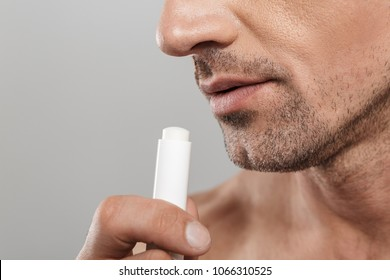 Cropped photo of of handsome mature man standing isolated over grey wall background naked holding lip balm.
