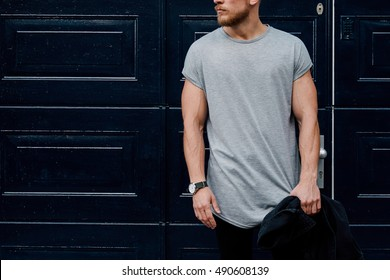 A cropped photo of a handsome muscular man wearing blank gray t-shirt while standing beside the dark blue entrance door on a street. Empty place for the logo or design. Mock up.