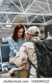 Cropped photo of happy female model looking down while sitting and holding her husband's arms indoors. American soldier is situating in front of his spouse. Homecoming concept