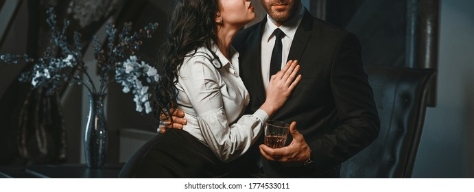 Cropped photo horizontal view couple in love hugging indoors. Sensual brunette and handsome businessman. Office romance concept