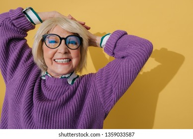 Cropped photo of joyful fashionable old lady in modern clothes situating in studio. She is smiling while raising her hands up and putting them on head against yellow wall